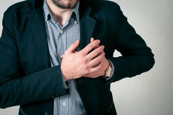 Man clutching chest with pain